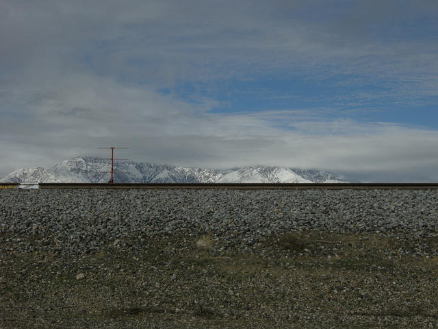 Tracks, Ballast, Marker Beacon, Mountains, Snow, and Clouds